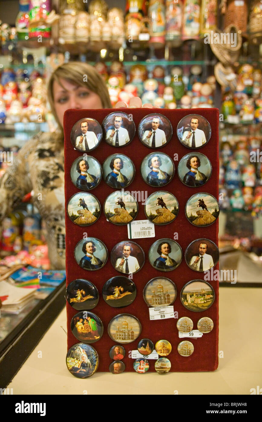 Shop assistant holding a display of badges of Peter the Great and Putin St Petersburg Russia - Stock Image