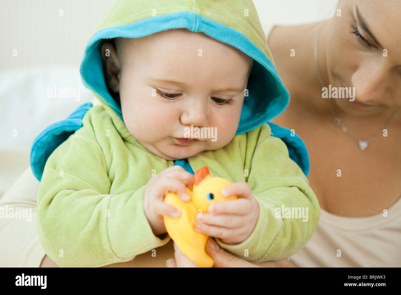 Baby playing with rubber duck before bathtime - Stock Image