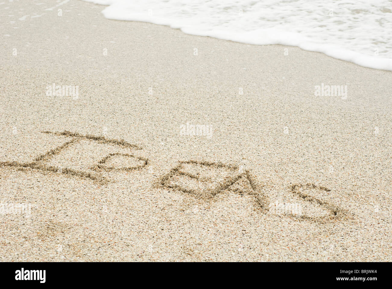 The word 'ideas' written in the sand at the beach - Stock Image