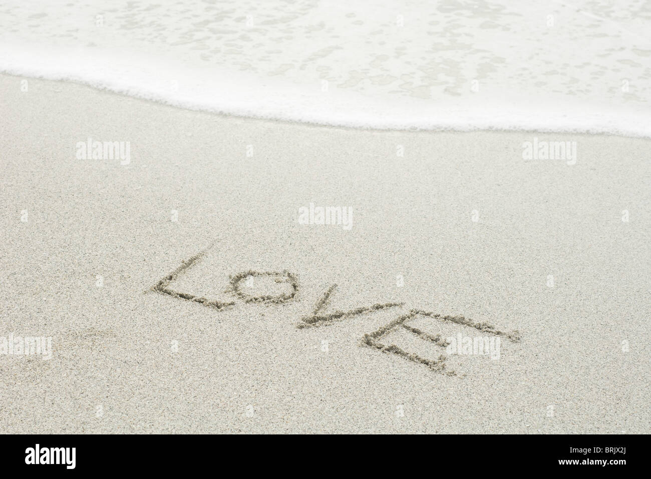 The word 'love' written in the sand at the beach - Stock Image