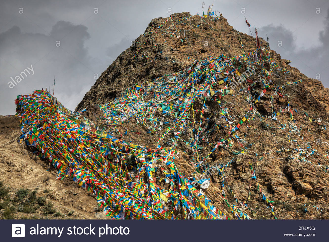 Prayer flags drape the mountain at Yumbu Lhakhang. Stock Photo
