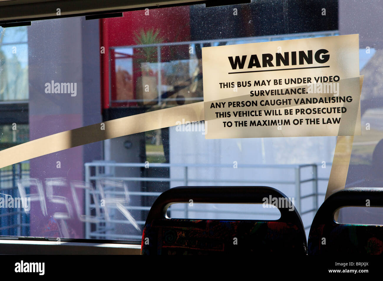 Video surveillance warning that all vandalism will be prosecuted next to graffiti scratched into the bus window - Stock Image