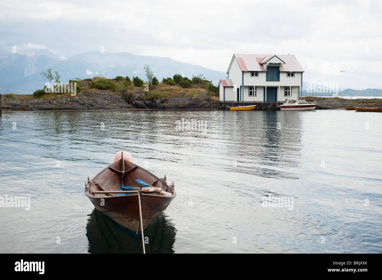 Boat with boat- and trade house in background by fjord at Onarheim, Hardanger in Norway. - Stock Image