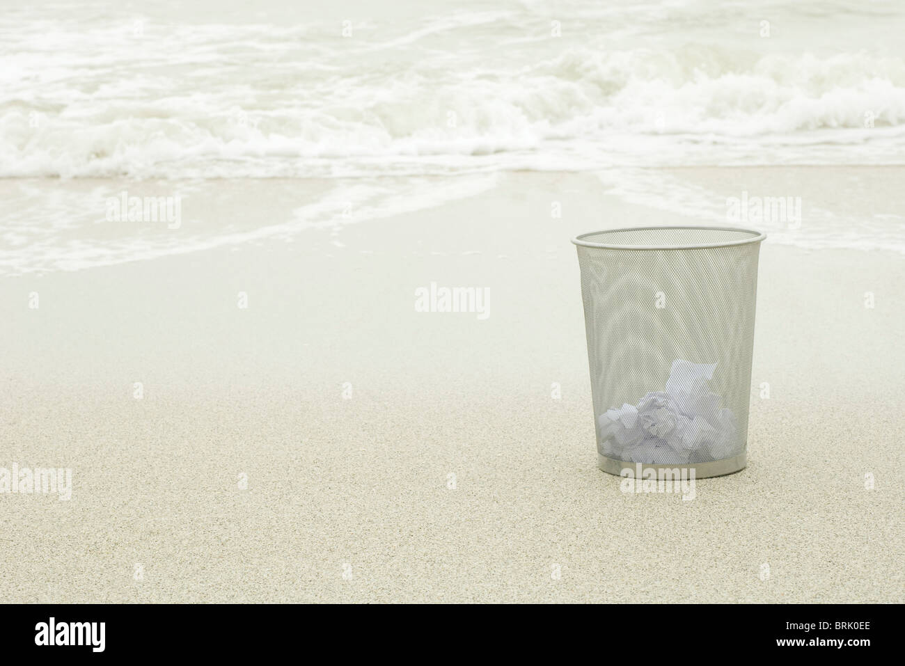 Wastepaper basket on beach - Stock Image