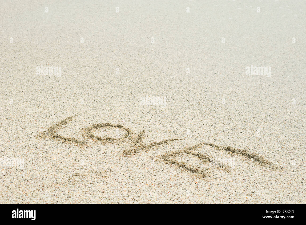 The word 'love' written in sand at the beach - Stock Image