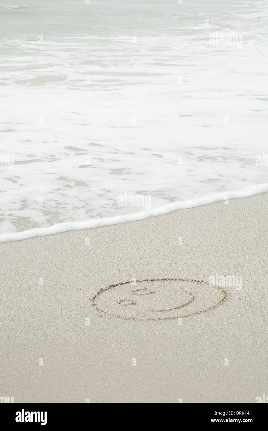 Smiley face drawn in sand on beach - Stock Image