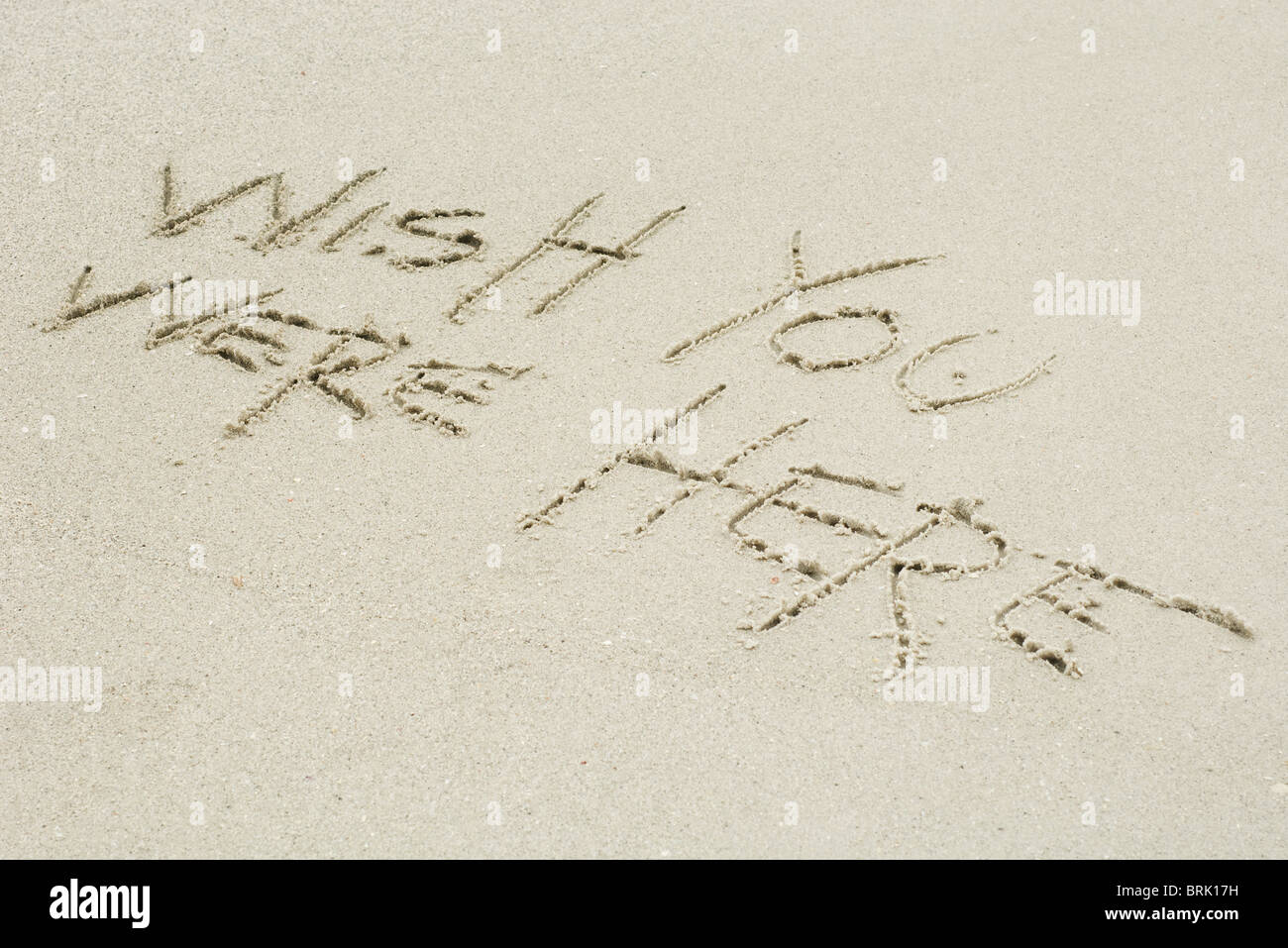 Wish you were here written in sand - Stock Image