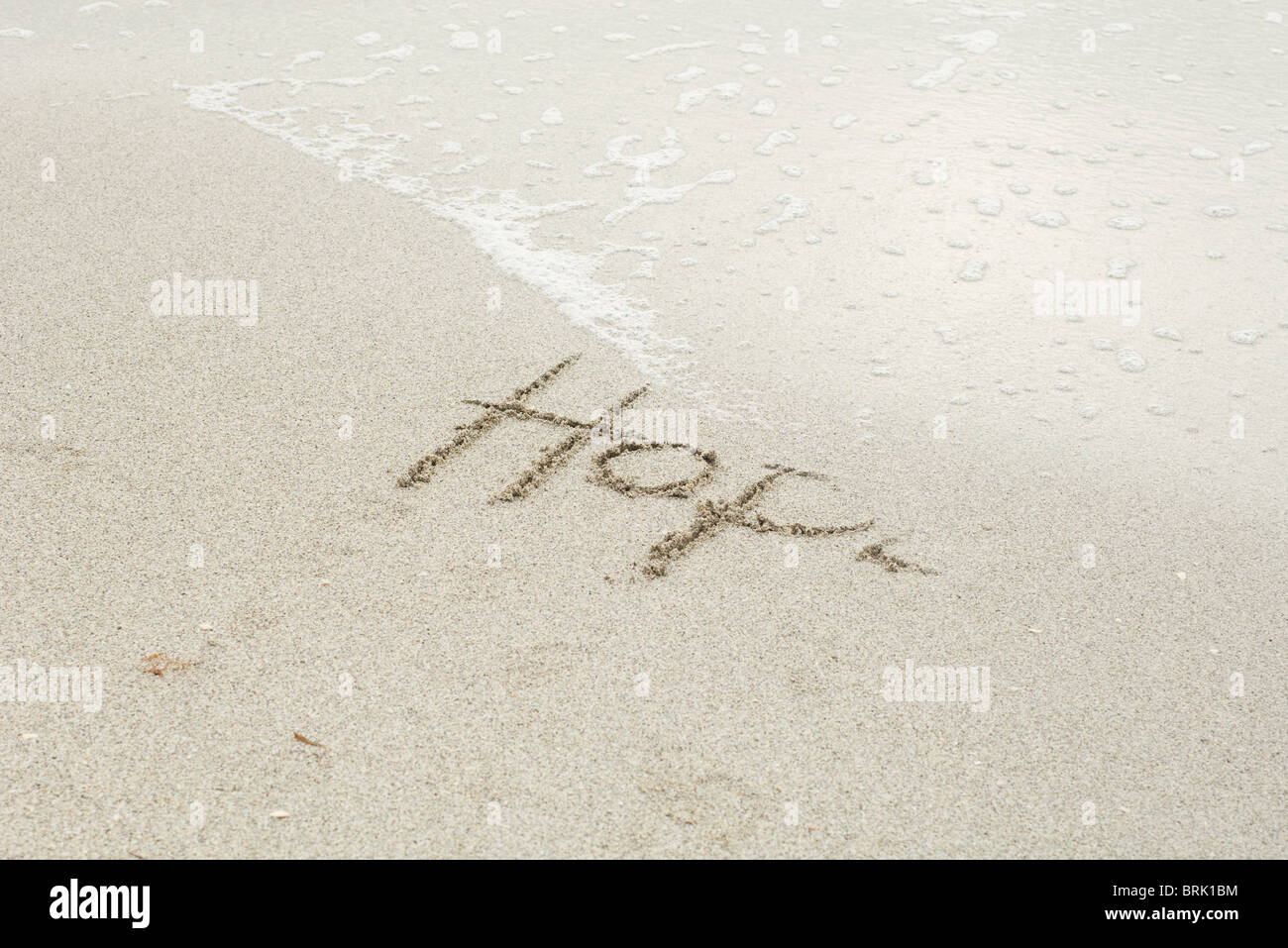 The word 'hope' written in the sand at the beach, partially washed away by the tide - Stock Image