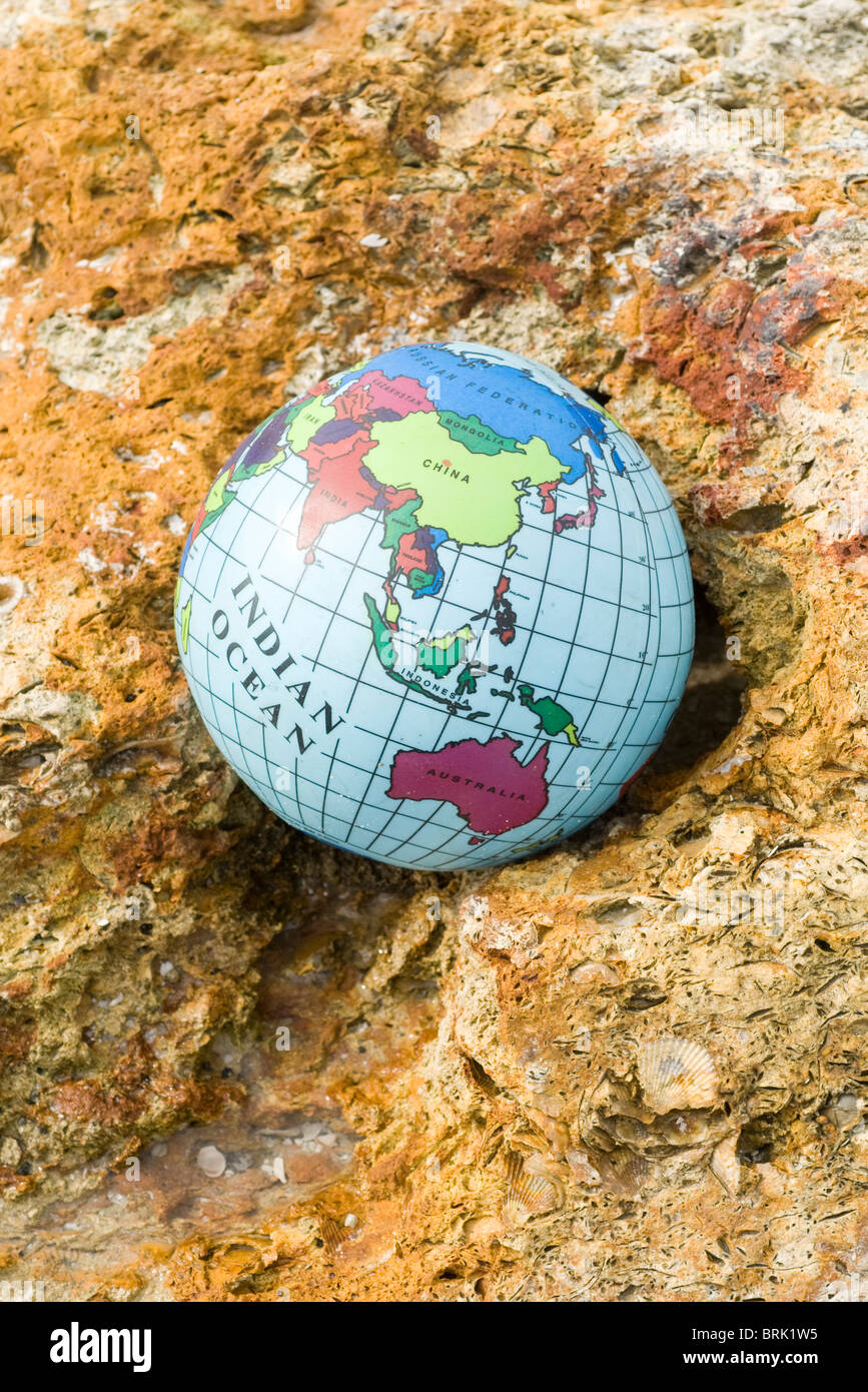Globe nestled in rock - Stock Image