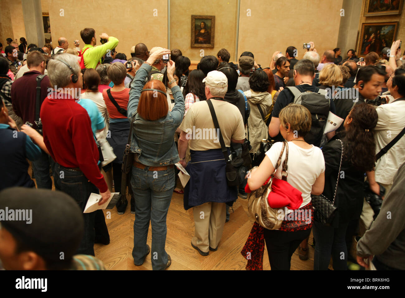 LOUVRE, PARIS, FRANCE-SEPTEMBER 20TH 2010: visitors trying to look at the Mona Lisa in the Louvre museum in Paris - Stock Image