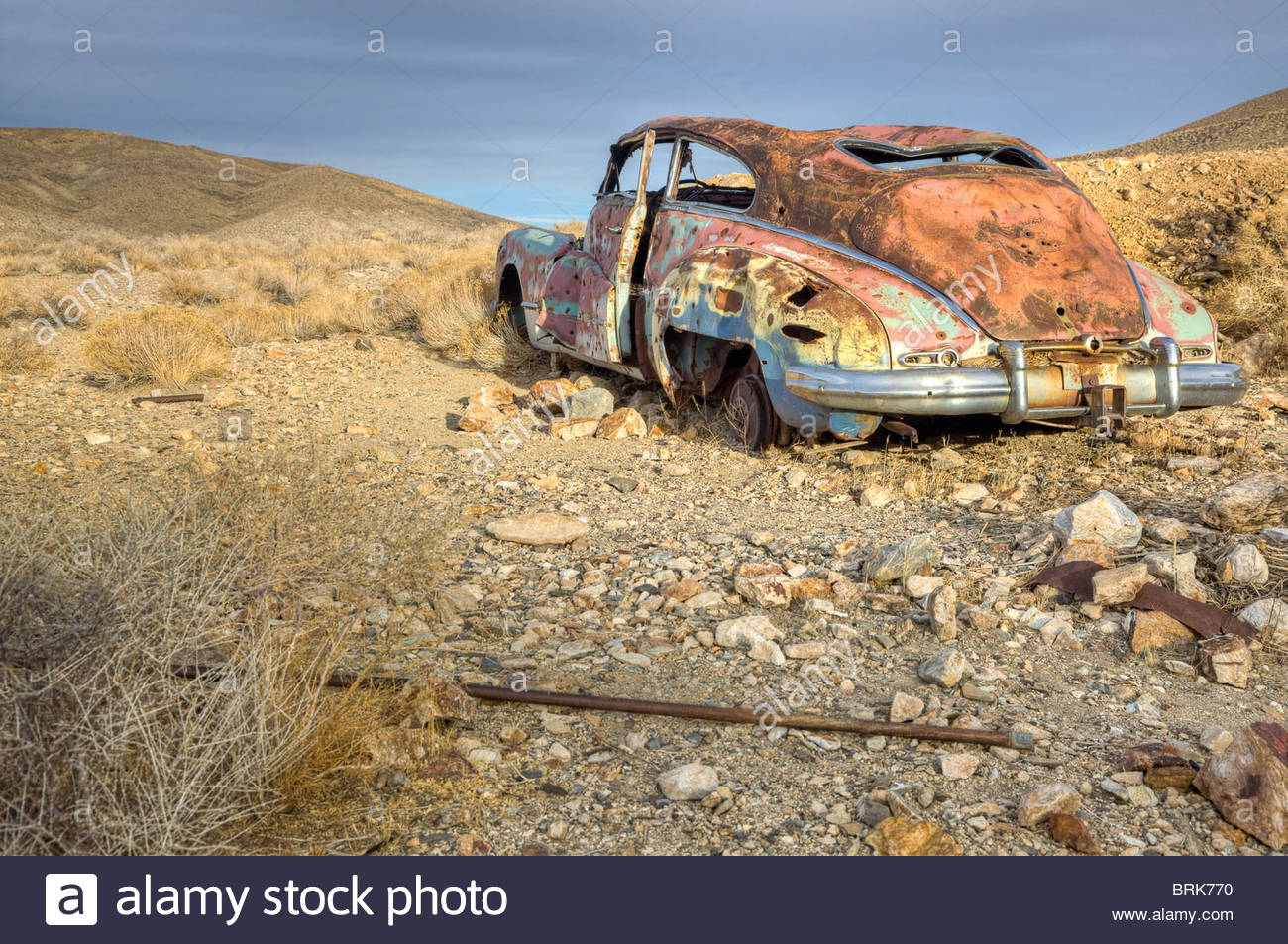An antique car sits abandoned and rusting in Death Valley. - Stock Image
