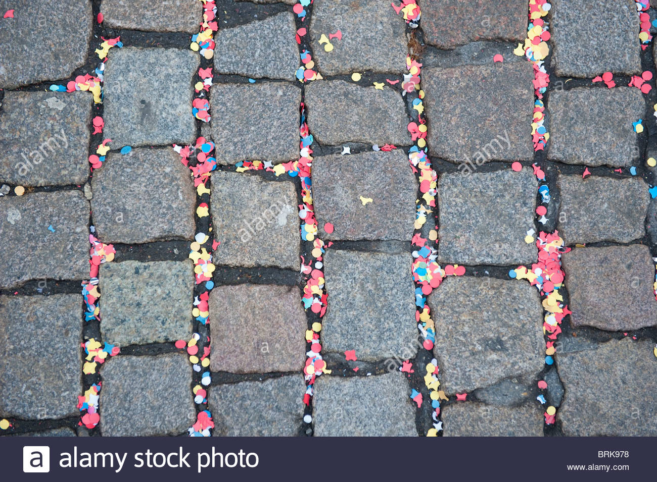 Confetti on a cobblestone street the morning after Carneval - Stock Image