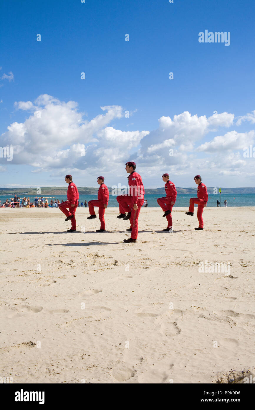 The Red Devils parachute display team march on Weymouth beach after a drop. - Stock Image