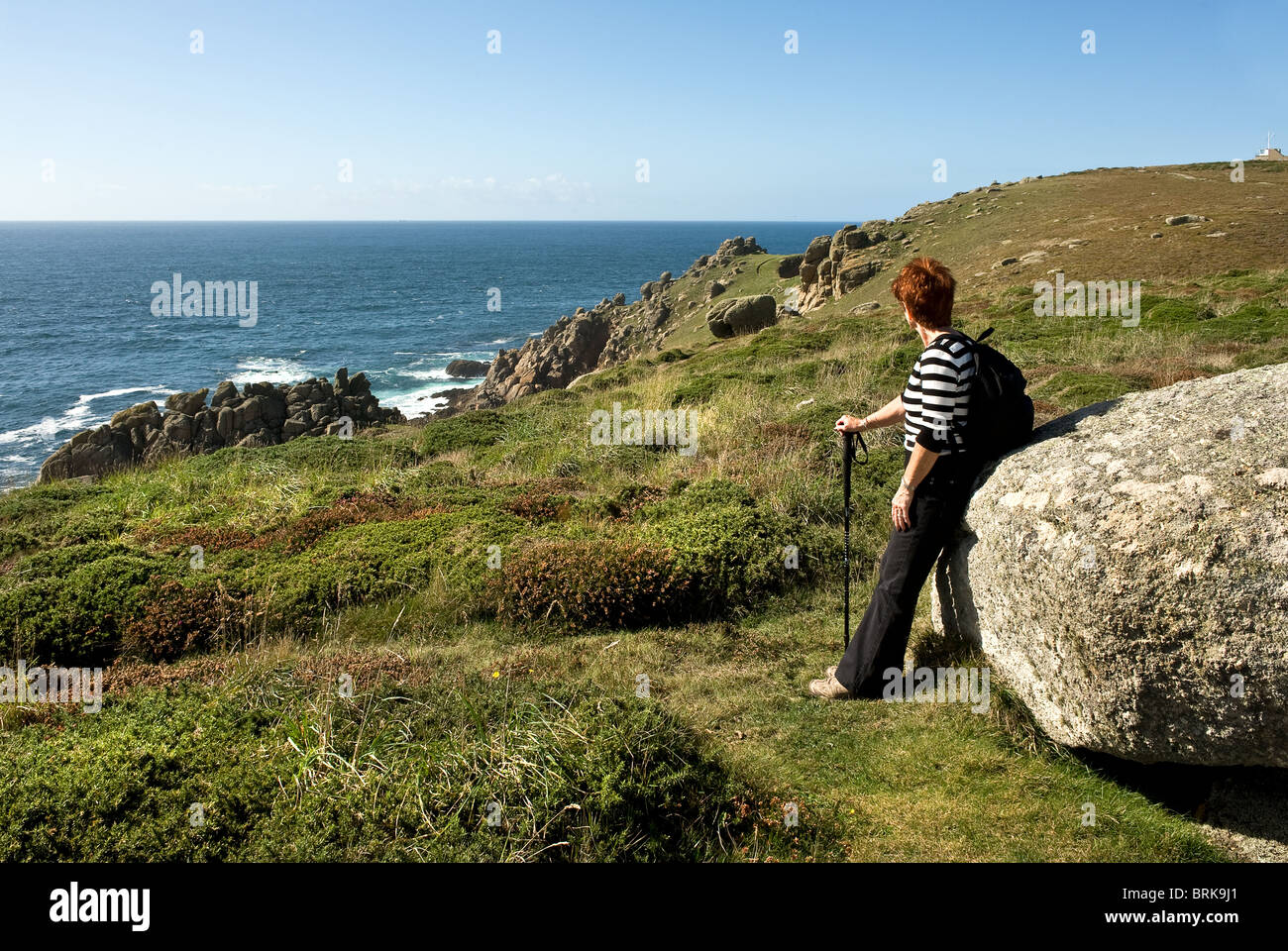 A walker resting against a granite boulder near Gwennap Head in Cornwall.  Photo by Gordon Scammell - Stock Image