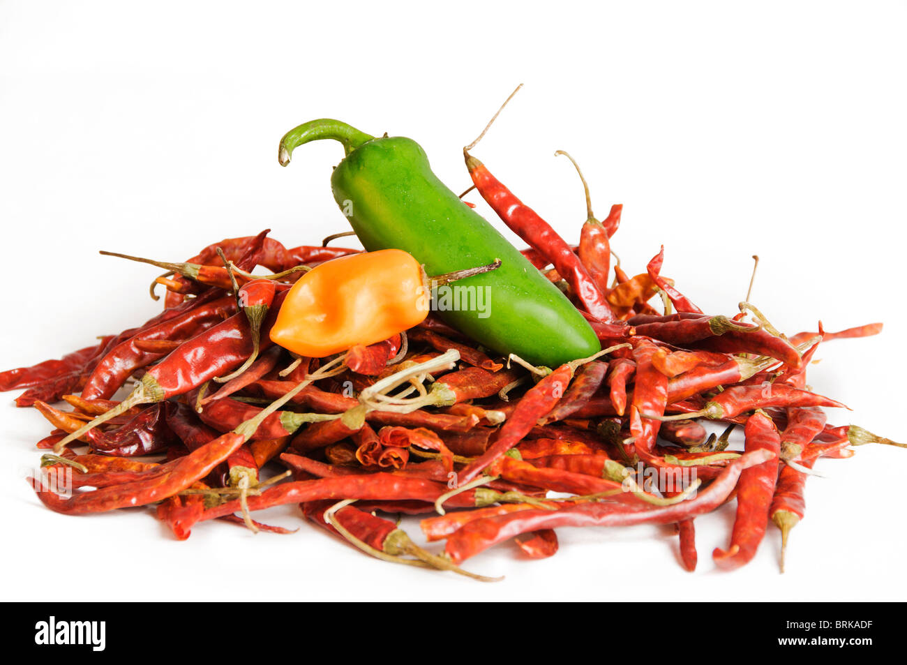 A combination of fresh and dried chilies are piled in a colorful display. - Stock Image
