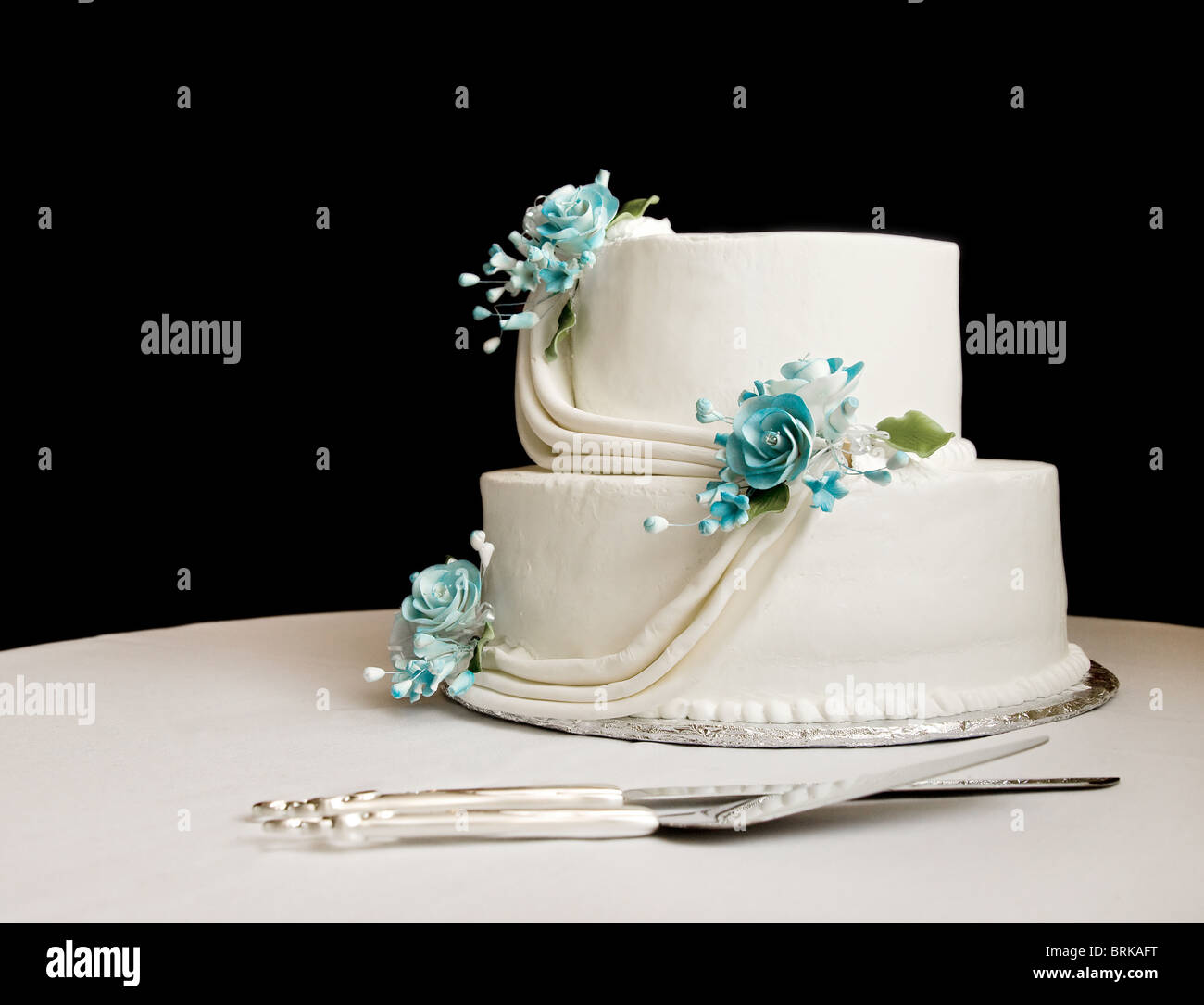 White wedding cake with blue flowers on a table with a black stock white wedding cake with blue flowers on a table with a black background izmirmasajfo
