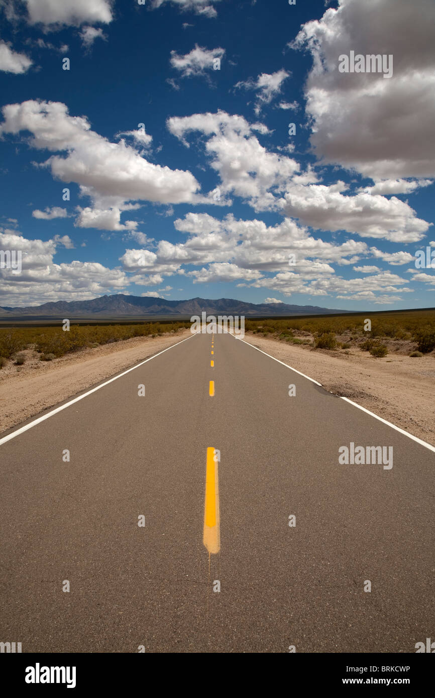 long deserted road in the Mojave Desert in California USA with mountains in the distance and fluffy white clouds - Stock Image