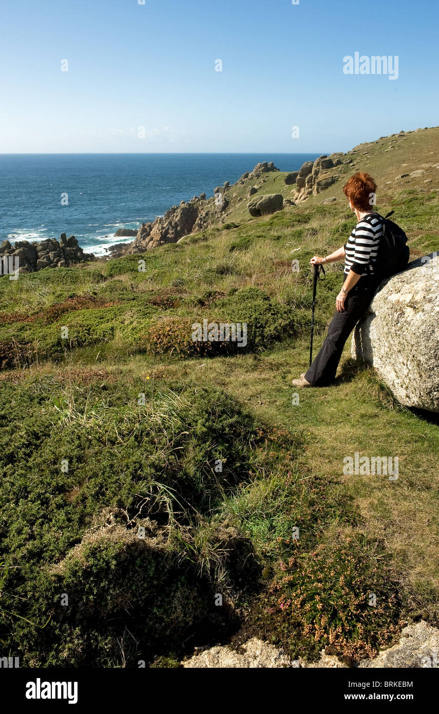 A walker resting against a rock on the South West coastal path in Cornwall.  Photo by Gordon Scammell - Stock Image