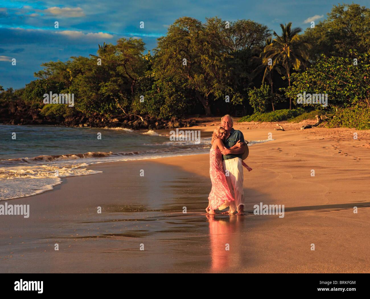 senior couple walking on a maui beach at sunset Stock Photo