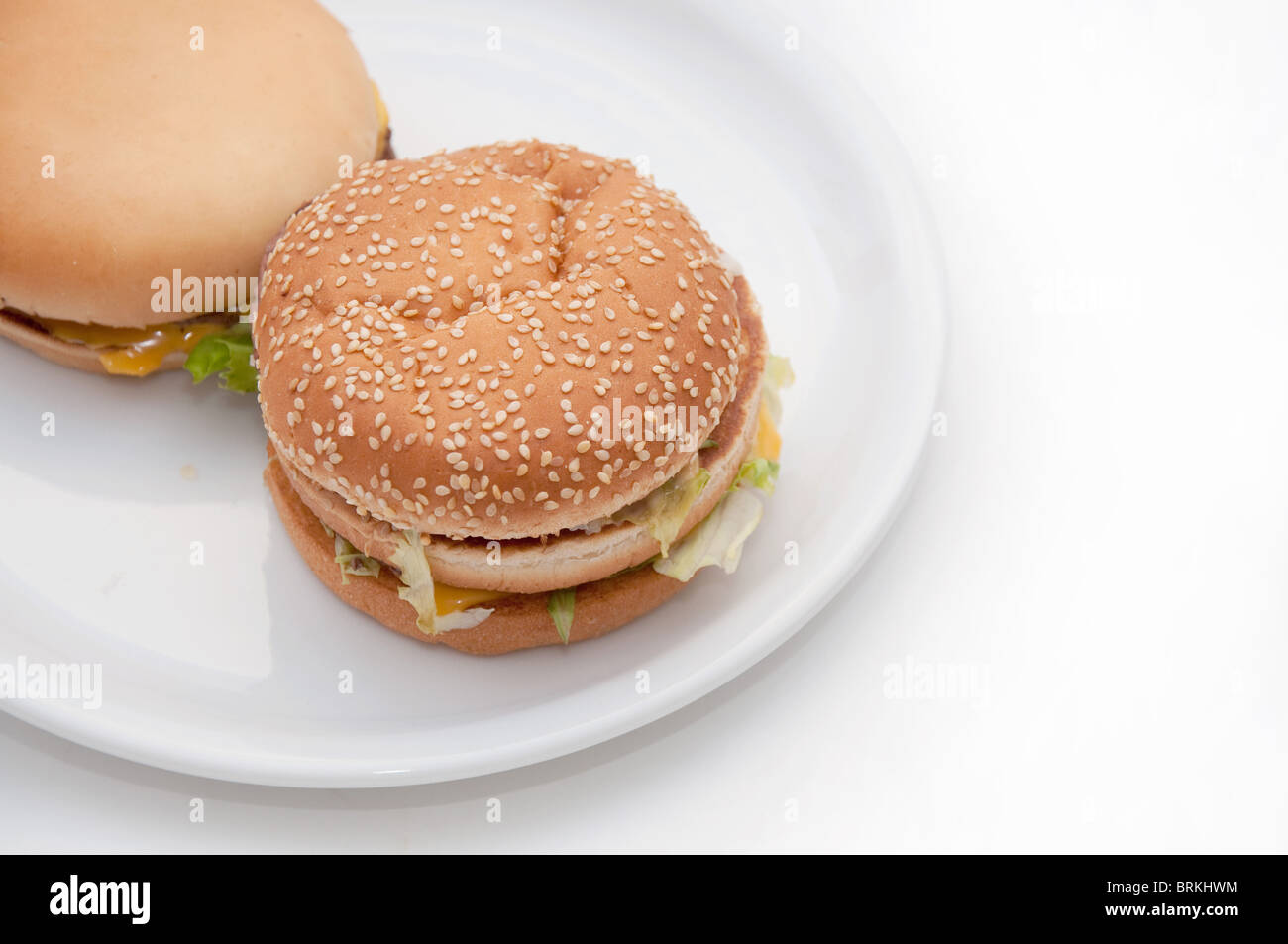 a tasty hamburger over white background. unhealthy junk food. - Stock Image