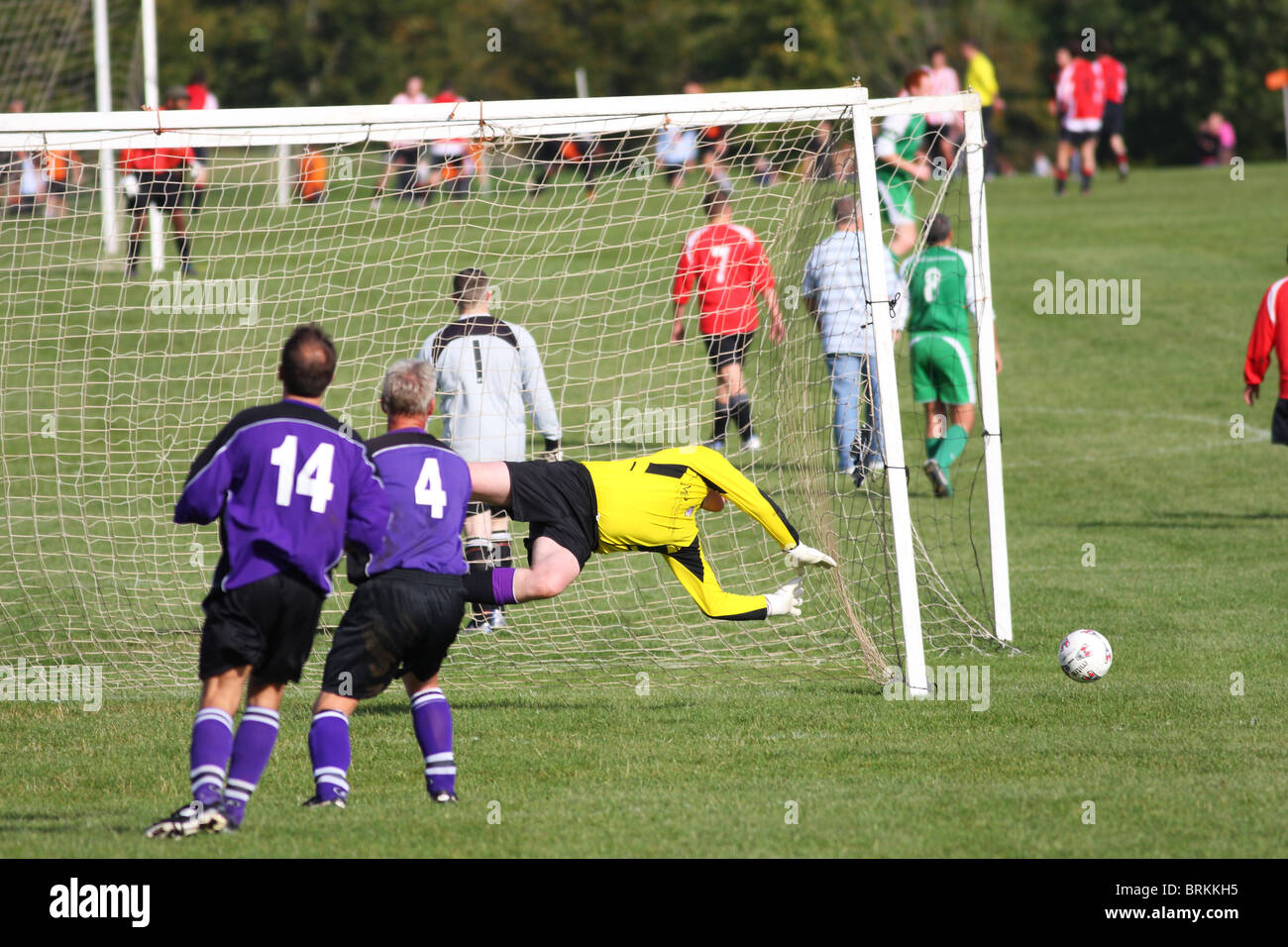 Shot of amateur footballers playing in the Downs League on a Saturday afternoon, the goalkeeper can be seen making - Stock Image