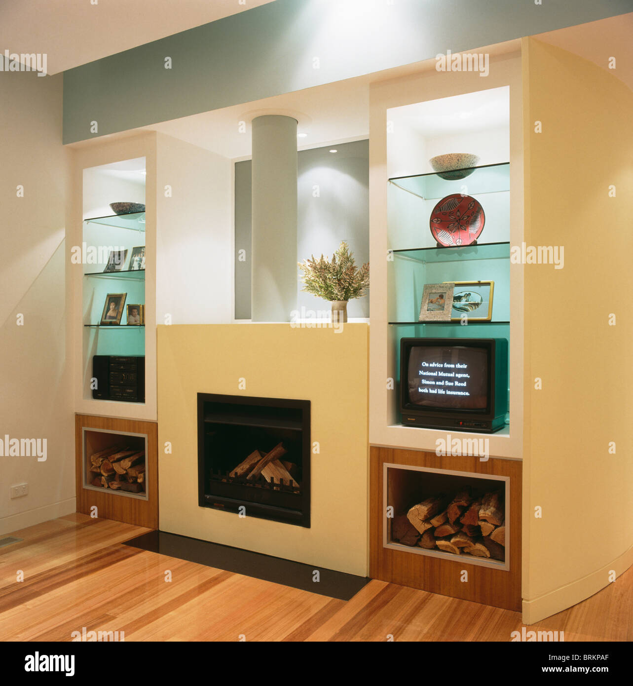 Logs Stored On Either Side Of Modern Fireplace In Wall With Lighting Above Glass  Shelves In Alcoves In Modern Living Room