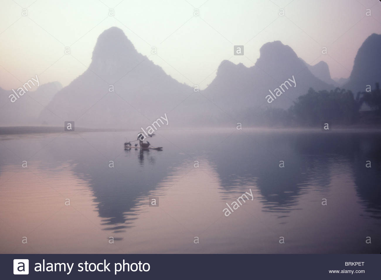 A cormorant Fisher, works the Li River at dawn. - Stock Image