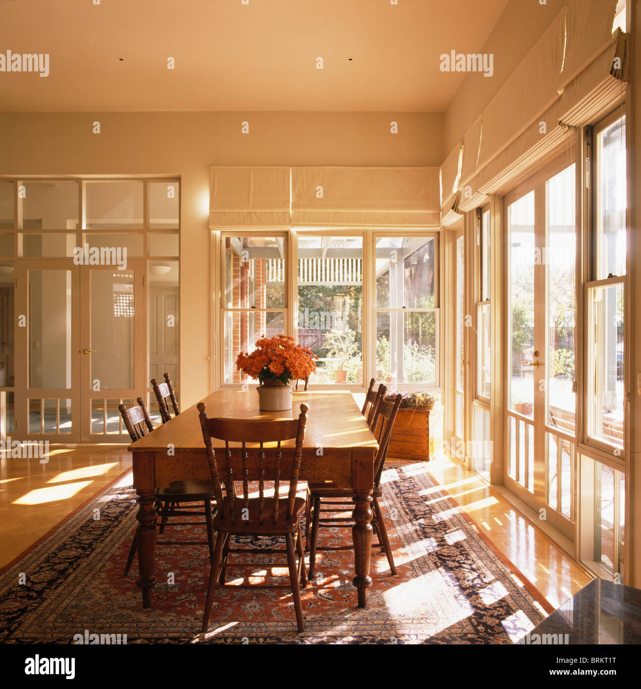 Old Wood Table And Antique Chairs In Large Modern White Dining Room With  French Windows And Glass Doors