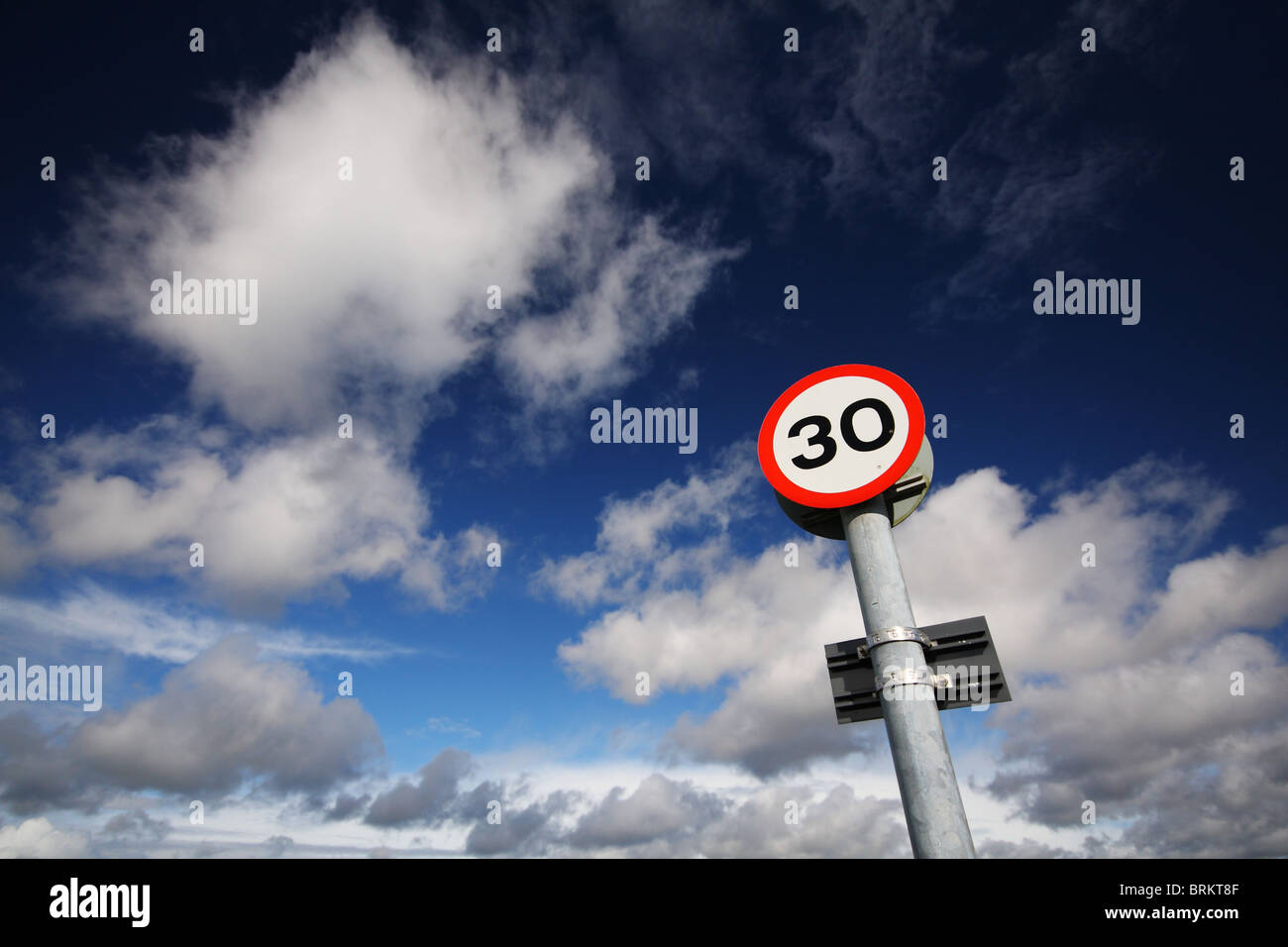 Shot of a 30 mph road sign set against a fantastic blue sky with white fluffy clouds. Stock Photo