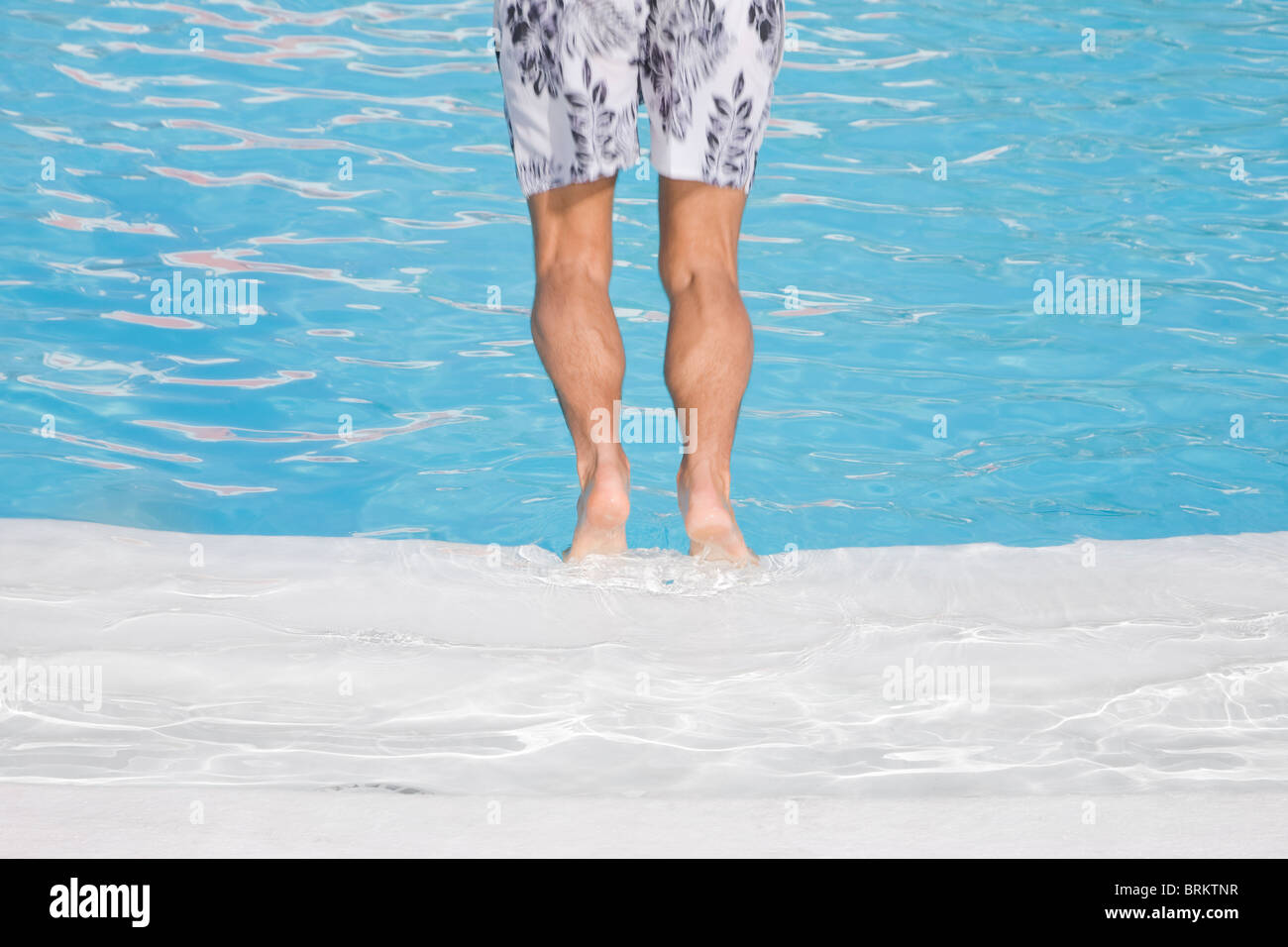 Man diving into a blue pool in black and white shorts - Stock Image