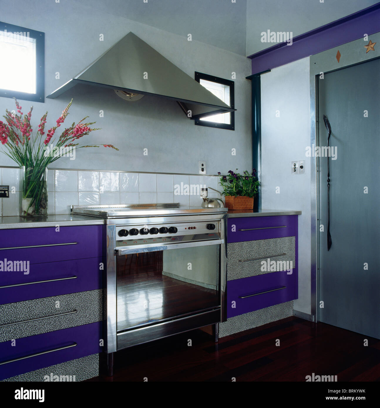Stainless steel extractor and range oven in modern kitchen with ...