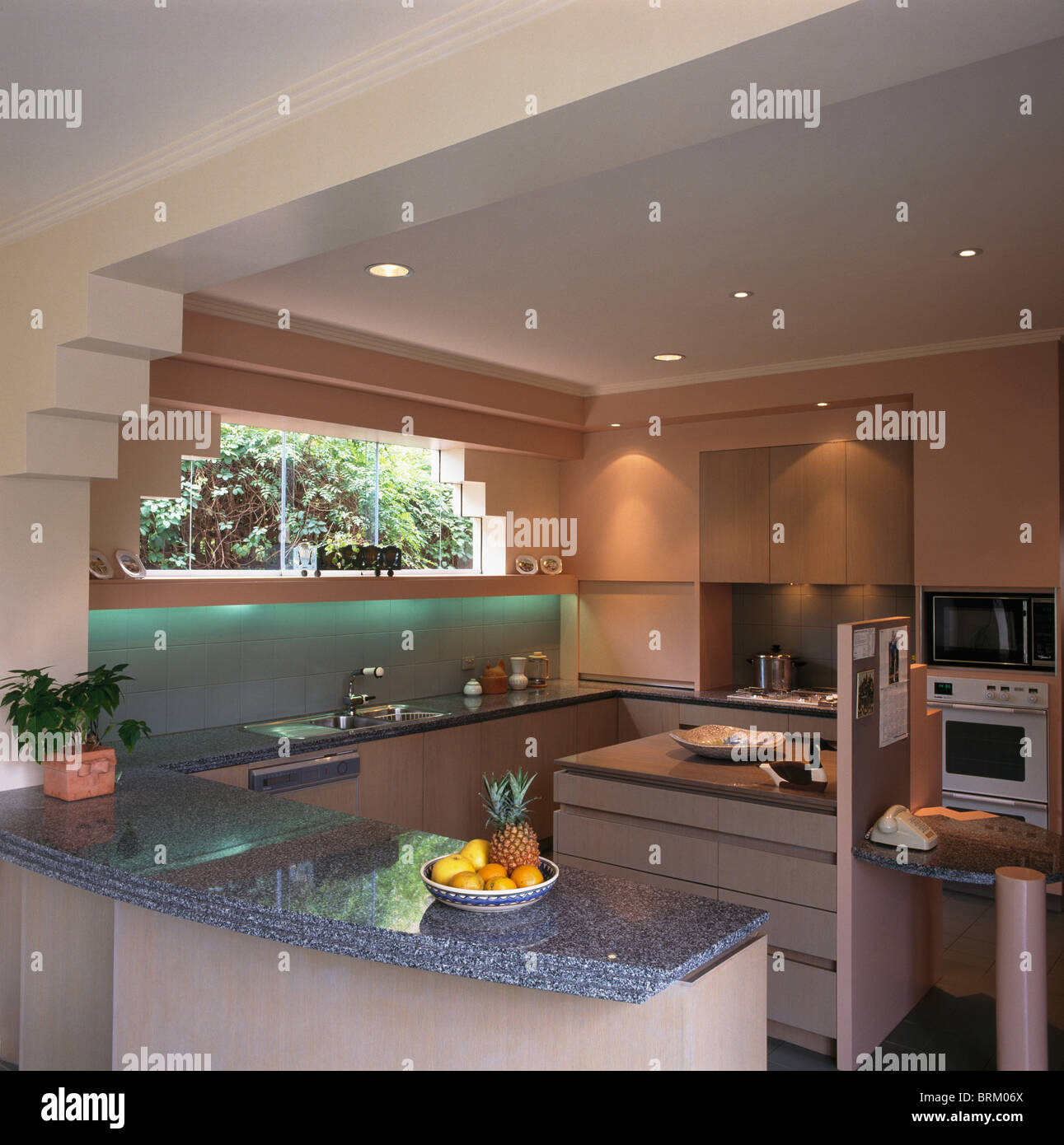 Kitchen Interior With Pink Furniture And Tiles Stock: Grey Granite Worktop On Peninsular Unit In Modern Pink