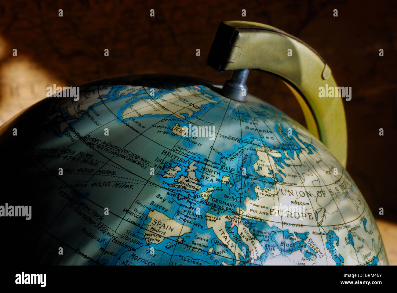 A small vintage globe of the Earth, highlighting the Northern Hemisphere and Europe, with an antique map as a background. - Stock Image