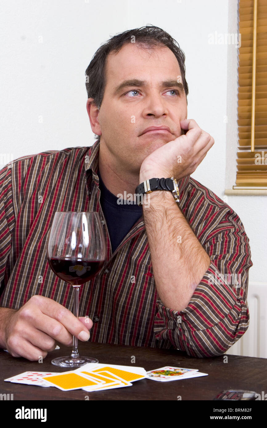 Male alcoholic drinking alone at home 40s - Stock Image