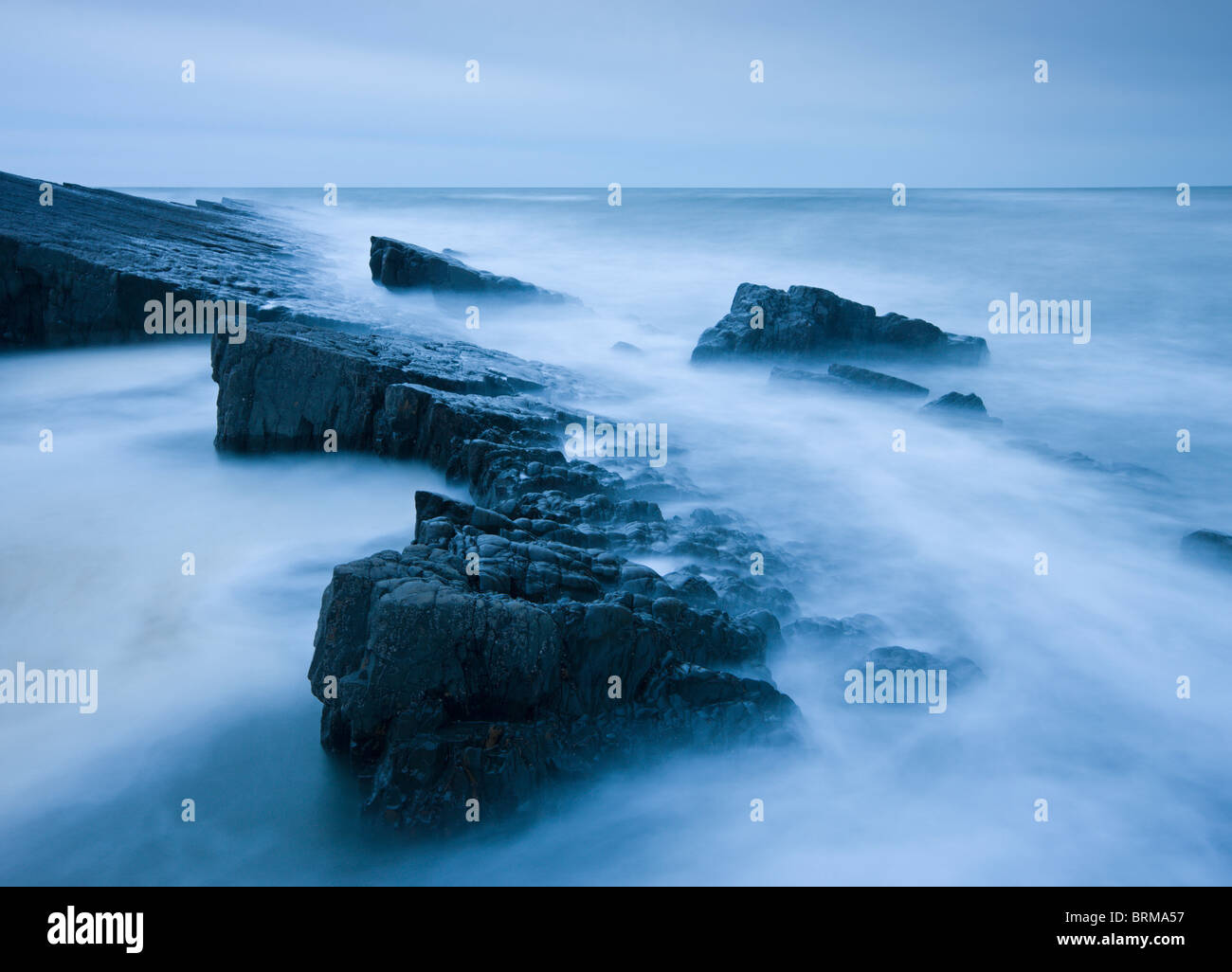 Swirling tide around jagged rocks on Spekes Mill Mouth beach, Hartland, Devon, England. Spring (April) 2010. - Stock Image