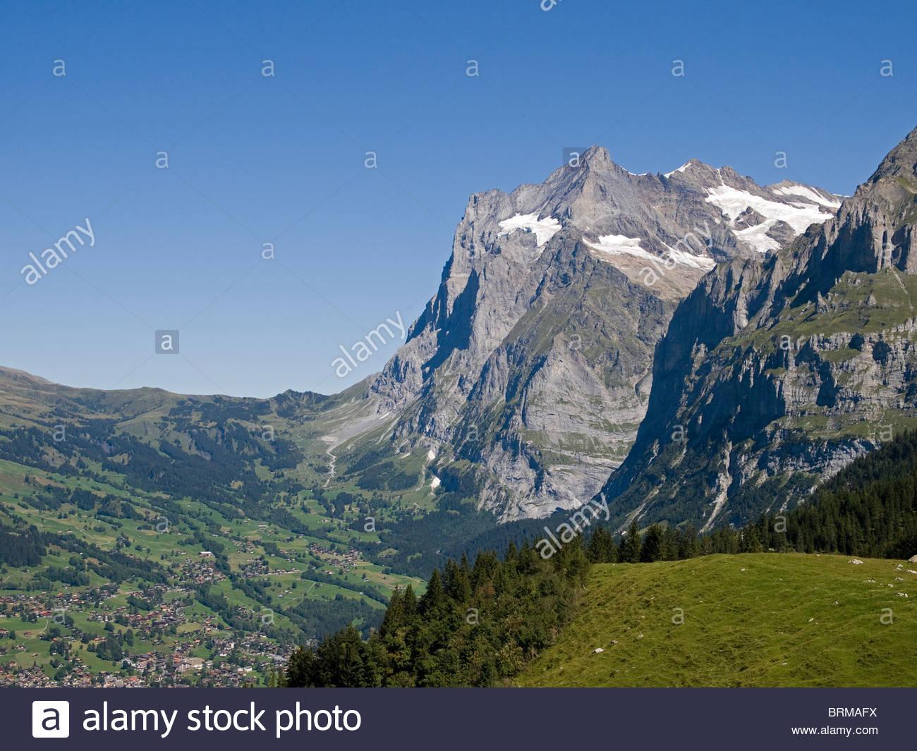 Grindlewald village below the Grosse Scheidegg and Wetterhorn - Stock Image