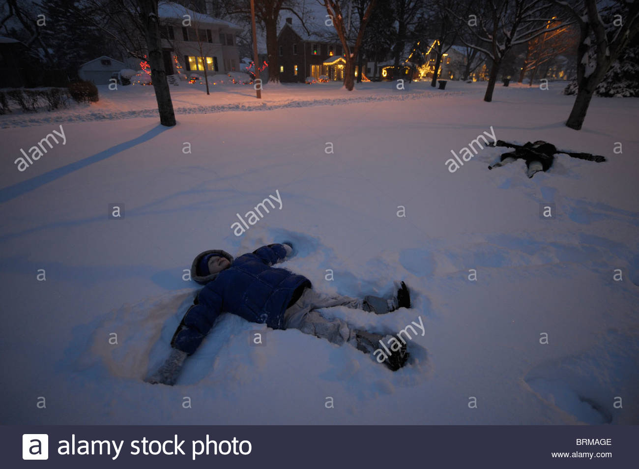 Two siblings make snow angels in their front yard in Lincoln, NE. - Stock Image