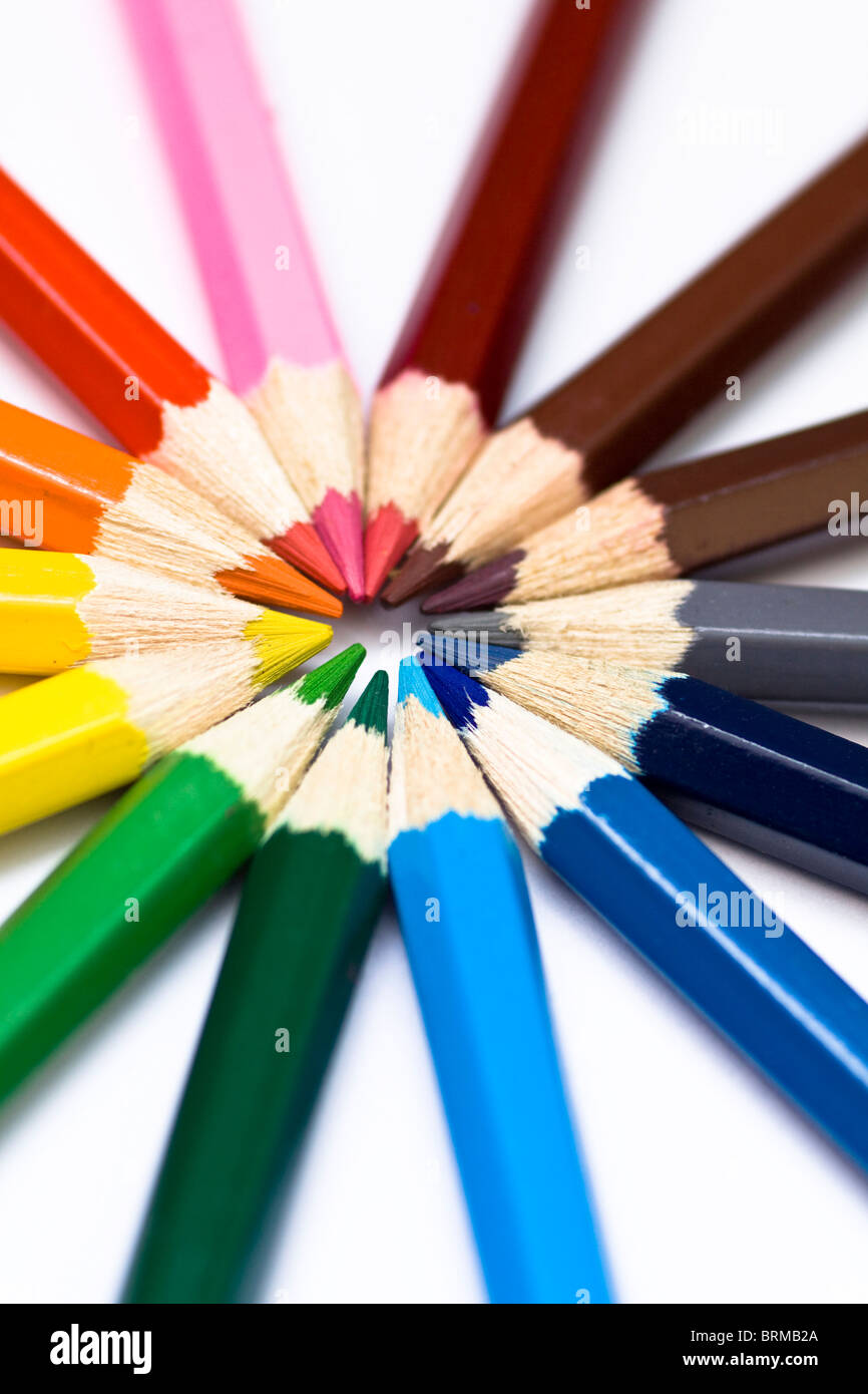 Close-up of a selection of colored pencil crayons, arranged like a color wheel. - Stock Image