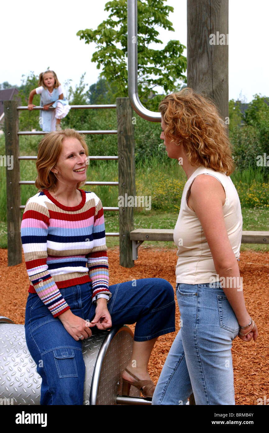 Mothers talking at playground and child playing and observing - Stock Image