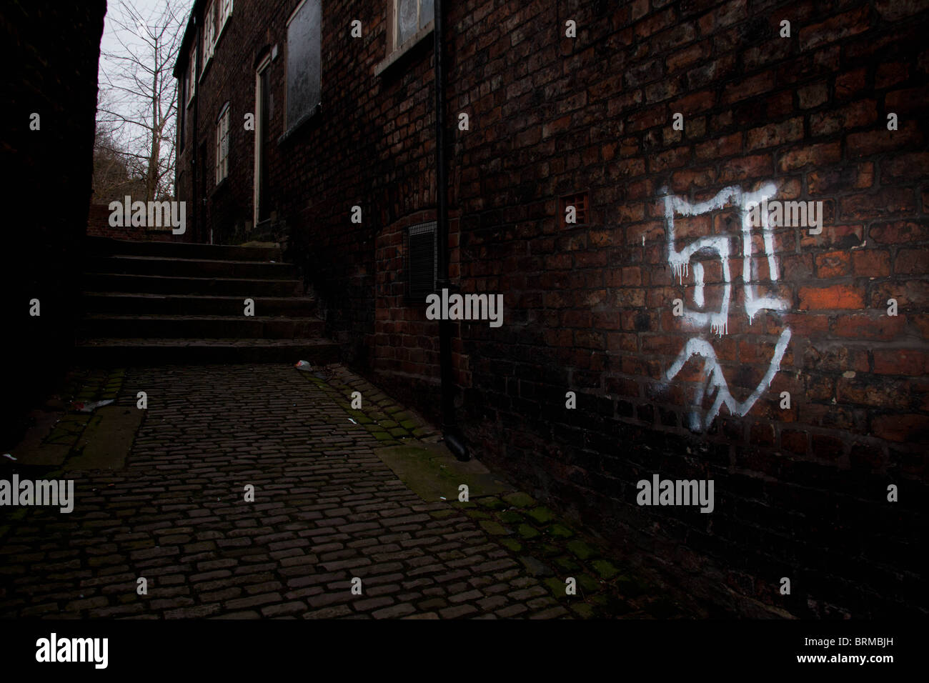 Graffiti on a red brick wall in a dark alley - Stock Image