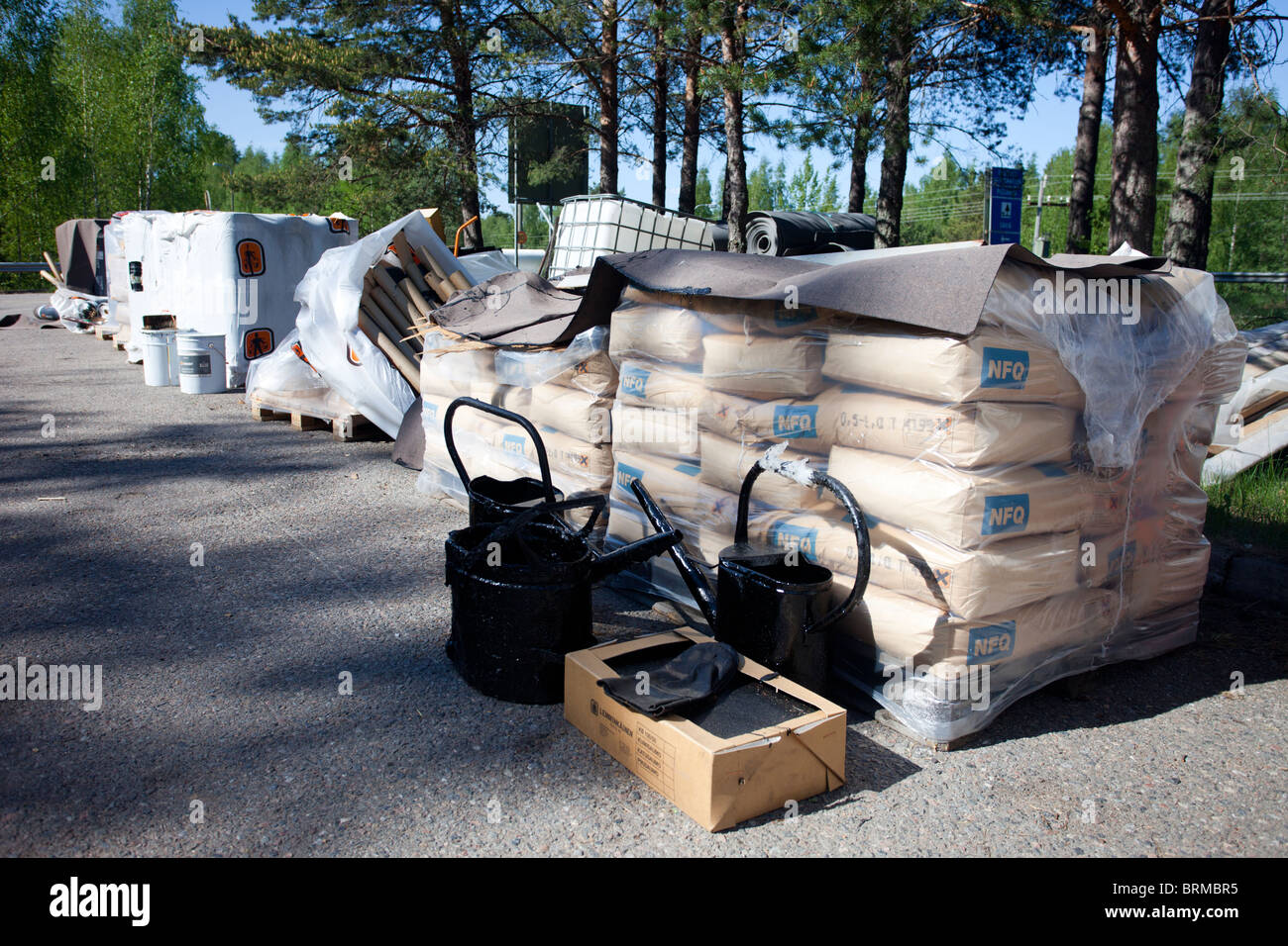 Materials used to fix the deck of a road bridge, cement sacks , pitch etc. , Finland - Stock Image