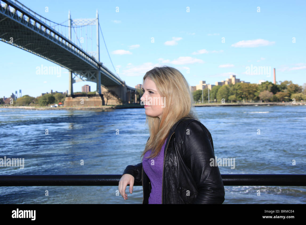 Attractive young blonde woman standing near Triboro Bridge along the East River in New York City, October 2, 2010 - Stock Image