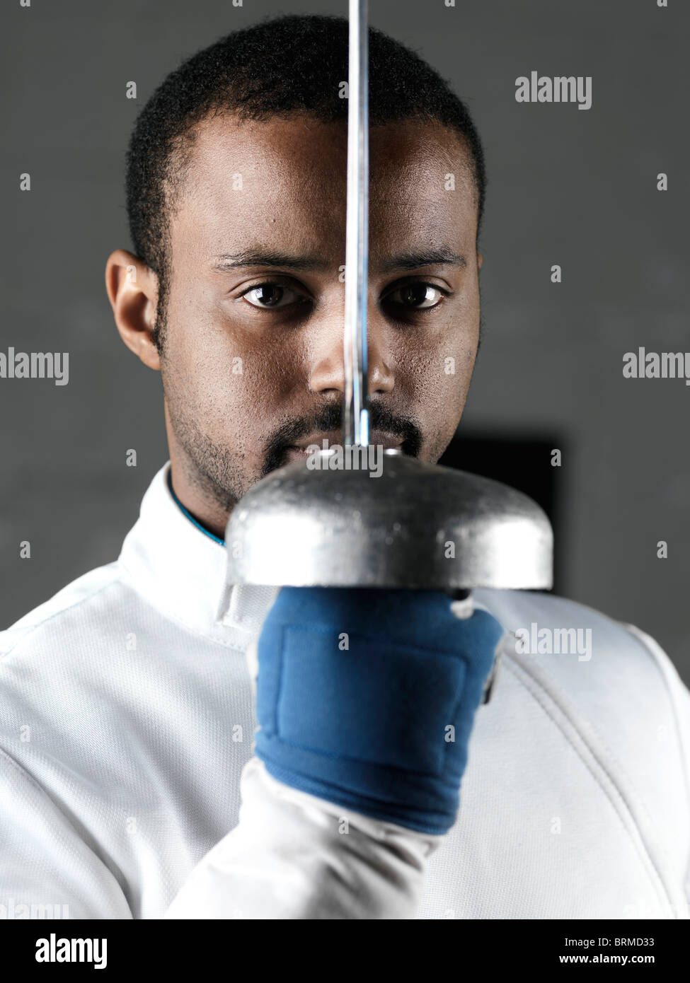 Portrait of a fencer holding an épée in front of his face - Stock Image