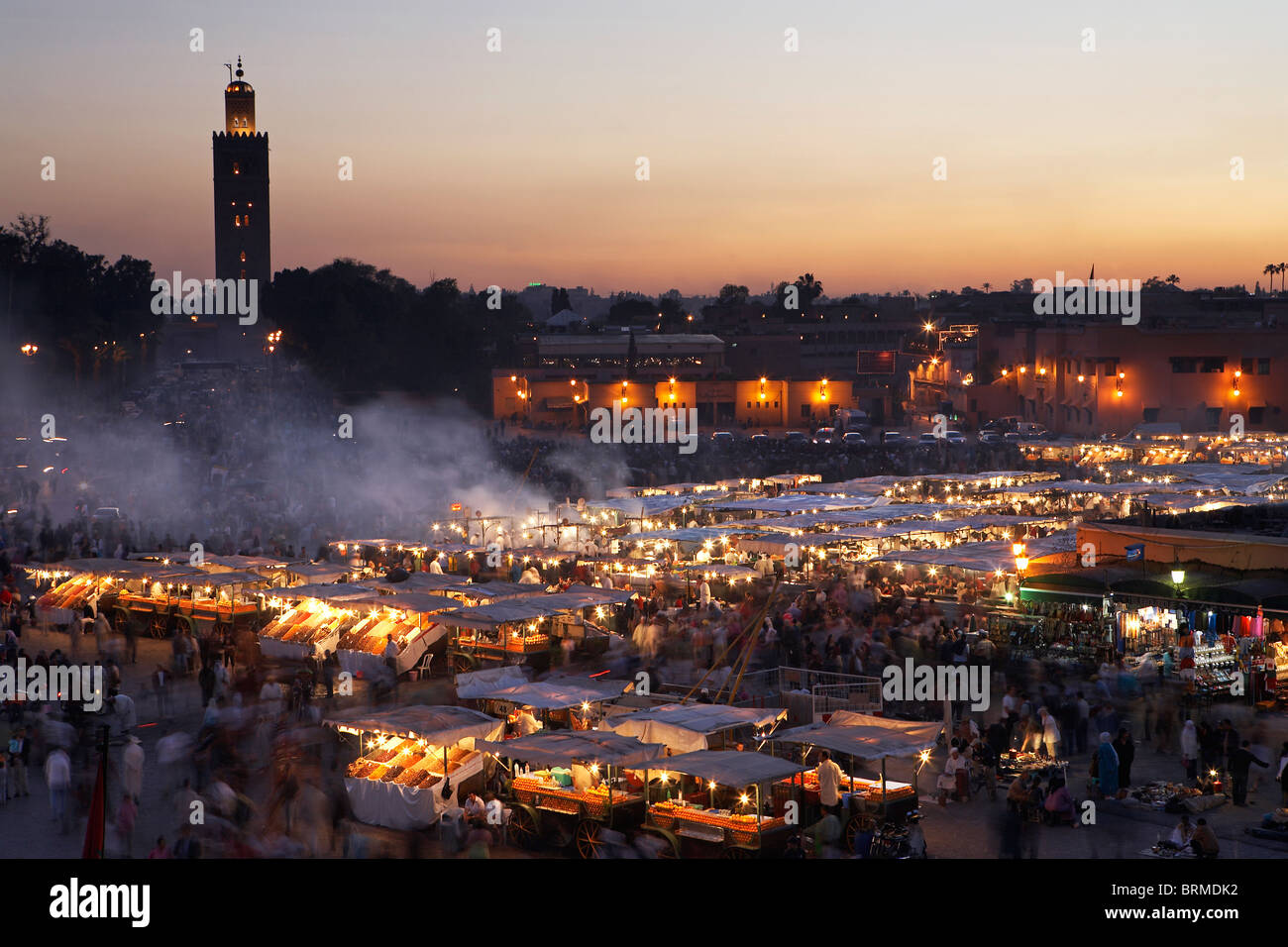 MARRAKESH: ELEVATED VIEW FOOD STALLS IN DJEMAA EL FNA AND KOUTOUBIA MOSQUE AT SUNSET - Stock Image
