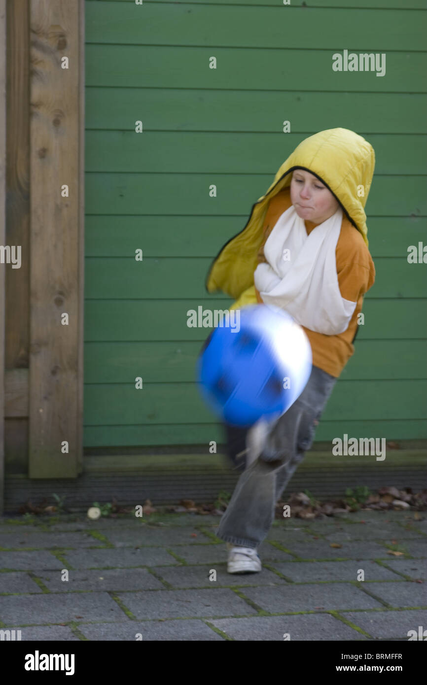 Rude young boy showing disrespect, kicking soccer ball, almost knocks me out. Stock Photo