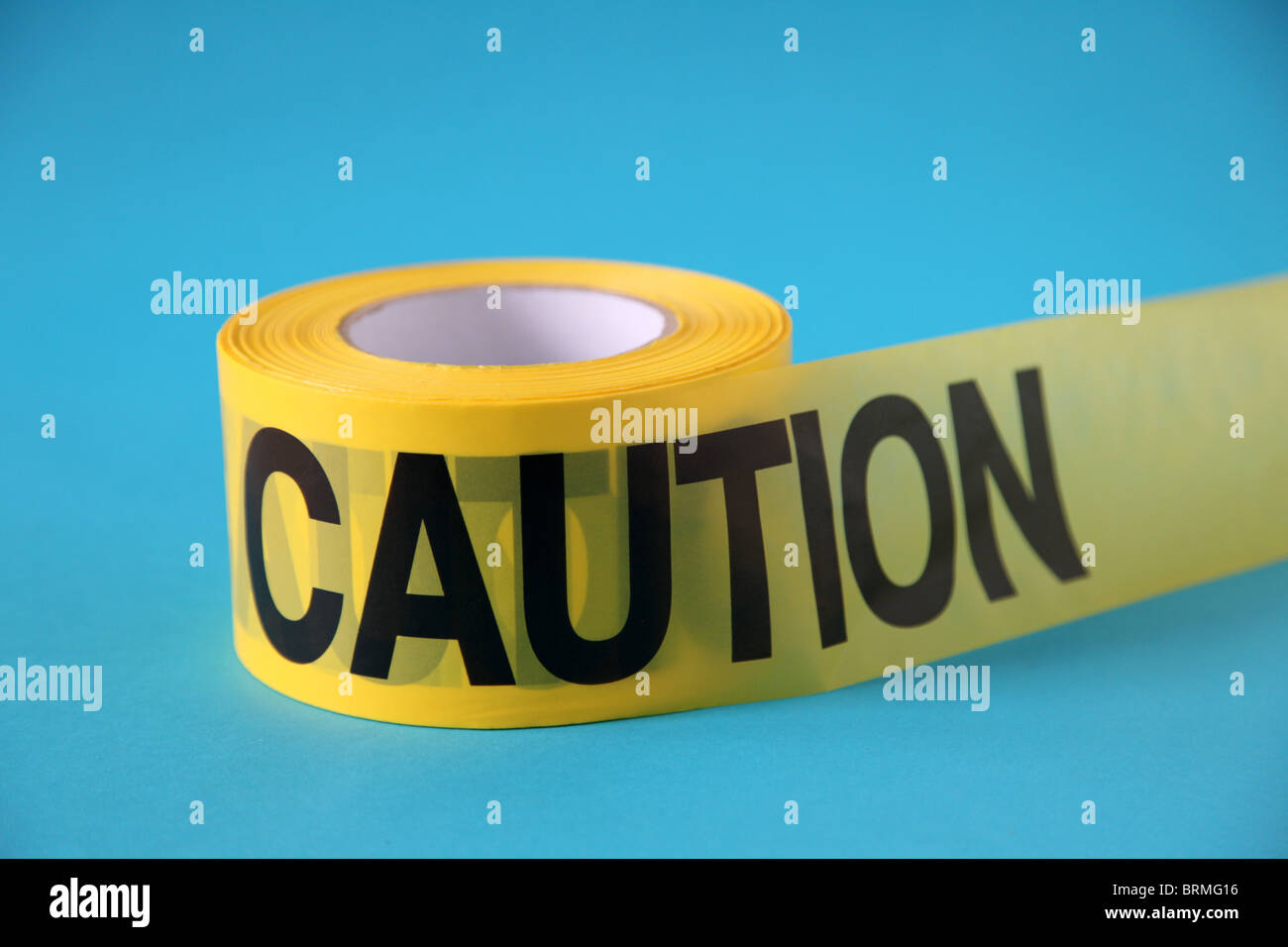 roll of CAUTION tape on blue surface - Stock Image