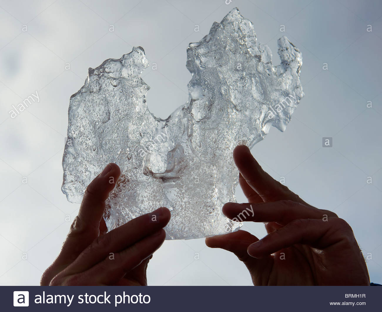Piece of glacial ice with air bubbles being inspected - Stock Image