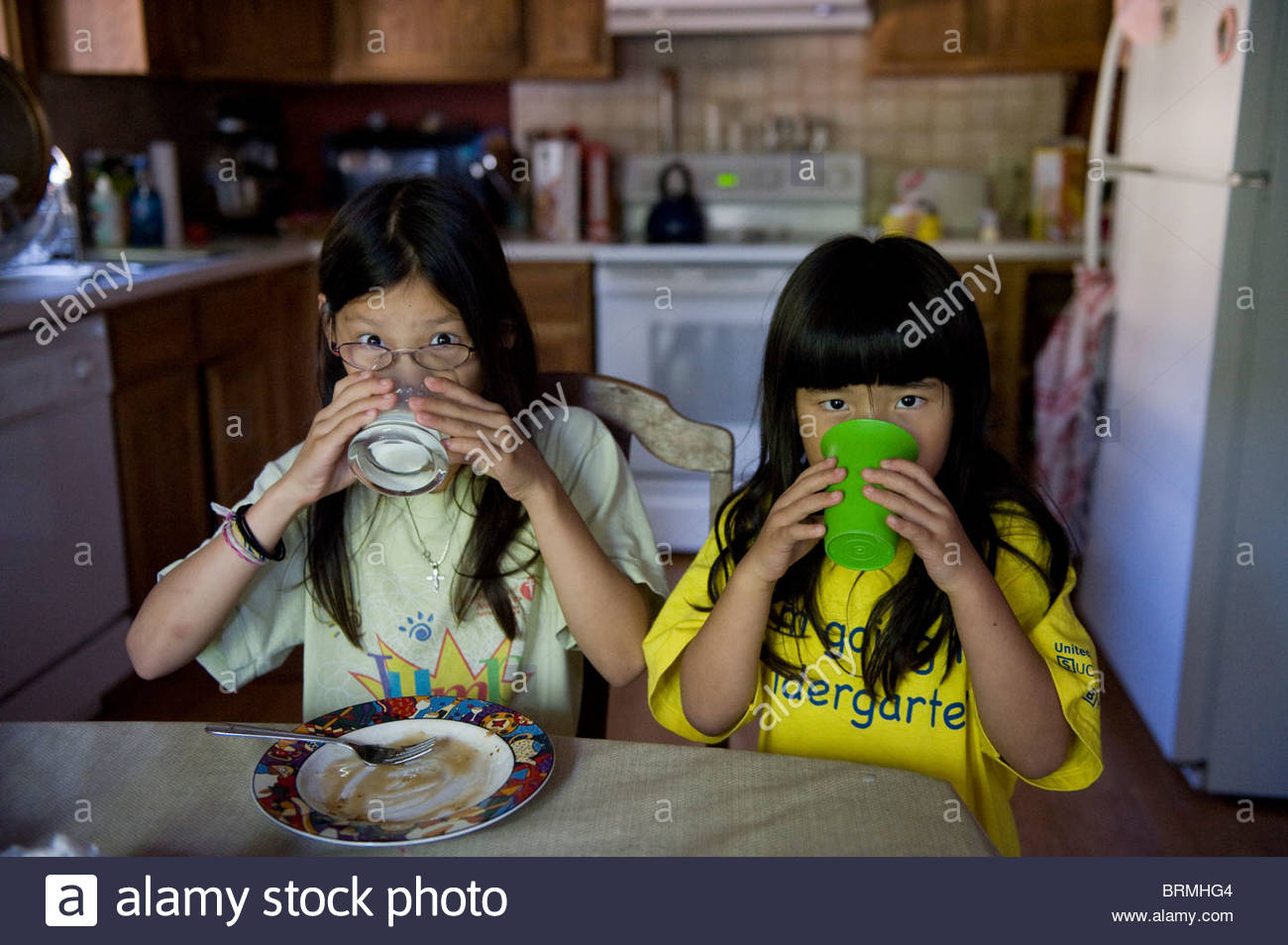 Two young girls drink their milk before heading to school. - Stock Image