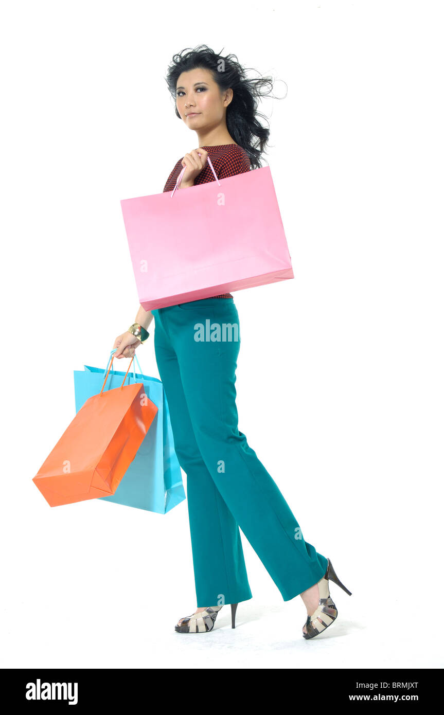 Woman carrying shopping bags and smirking - Stock Image