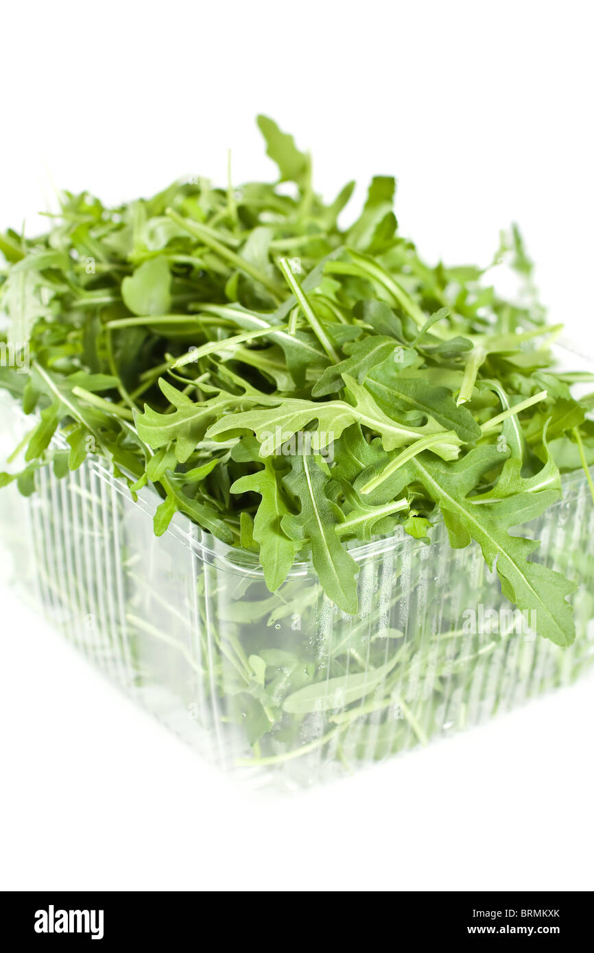 Rocket leaves In A Plastic Container Isolated On White - Stock Image